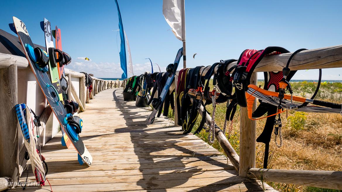 massor av kitesurfprylar vid stranden
