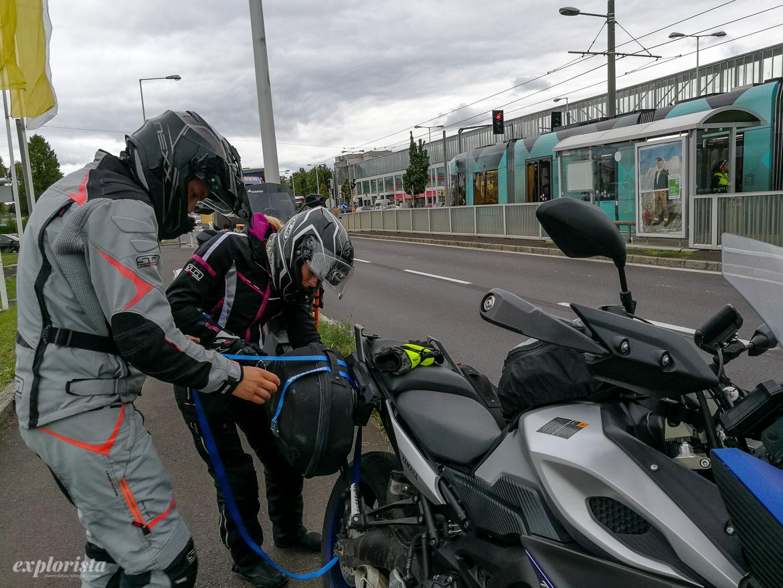 Två MC-åkare sätter fast sidoväska med spännband