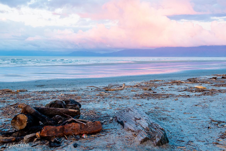solnedgång över strand i nya zeeland