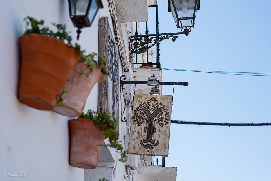 skylt och blomkrukor på vägg
