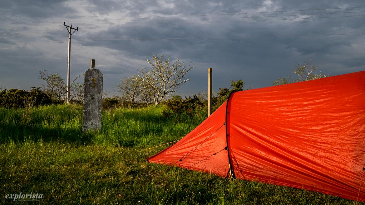 rött tält mot grå himmel